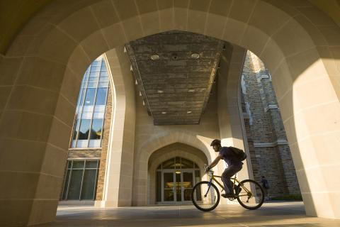 Person bicycling through walkway on campus