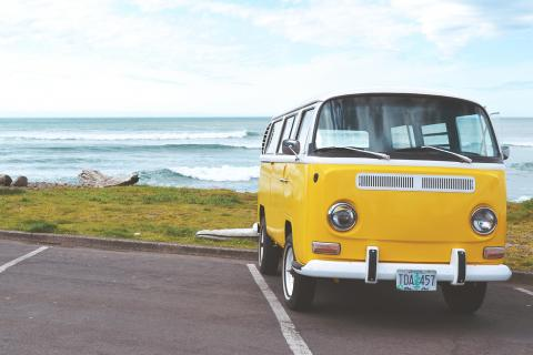 Yellow VW bus in parking lot near ocean